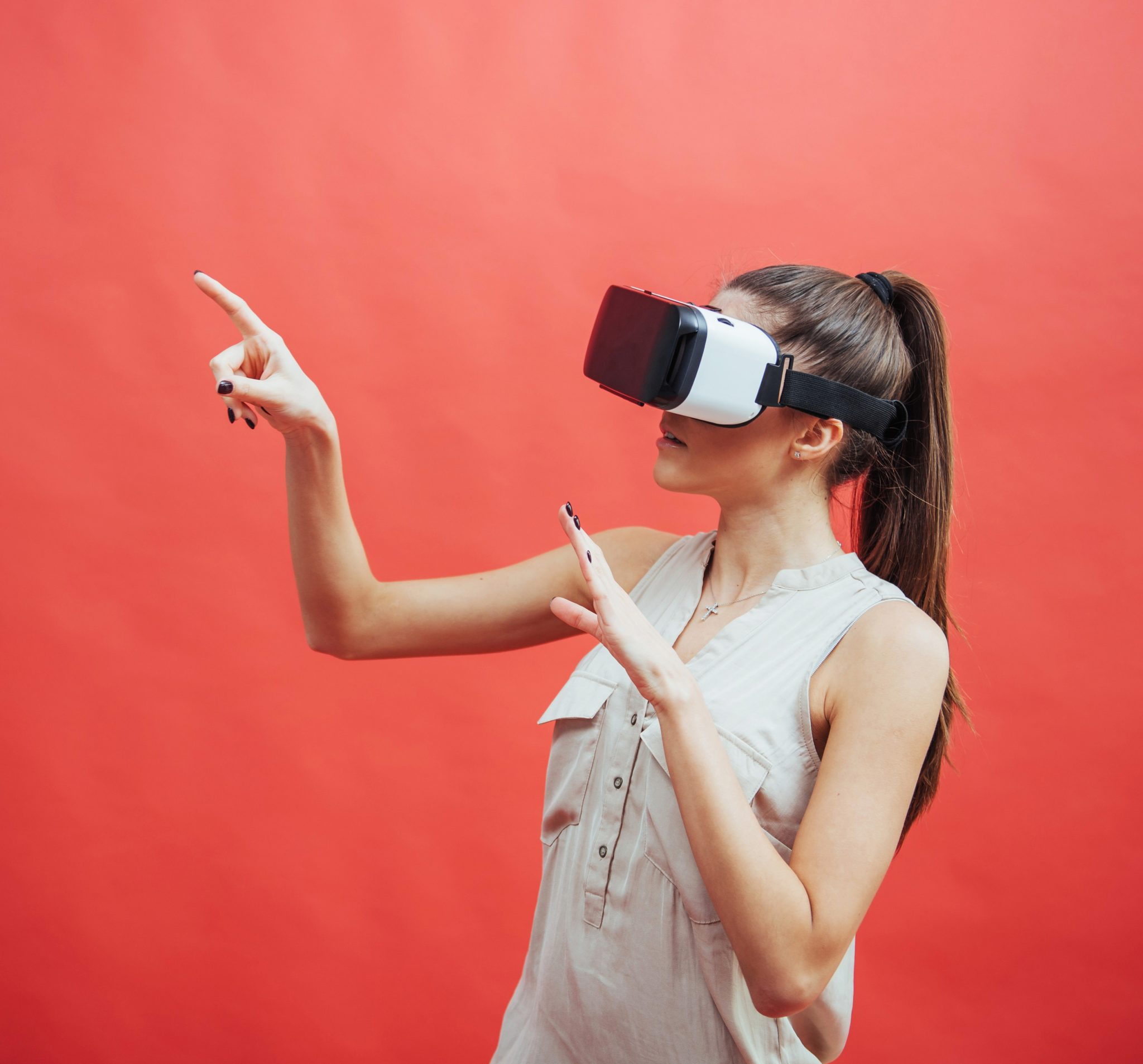 portrait of happy smiling young beautiful girl, gain experience using VR-headset virtual reality glasses, isolated on a red background